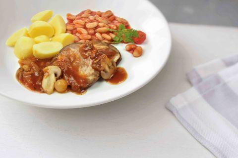 Varkenslapje met witte bonen in tomatensaus en gekookte aardappelen