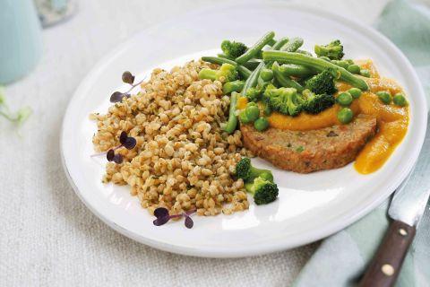 Groenteburger met groene groenten, wortelsaus en spelt