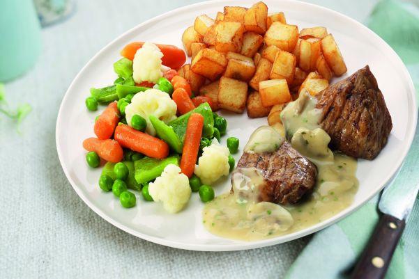 Varkenhaas in champignonsaus met een groentemix en gebakken aardappelen