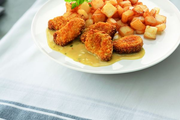 Kipnuggets in kerriesaus gebakken aardappelen gekruid