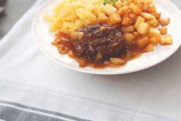 Hamburger in uiensaus met appelmoes en gebakken aardappelen
