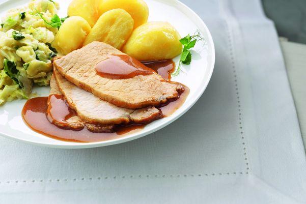 Gesneden varkensvlees met savooiekool en gekookte aardappelen