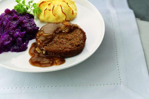 Vegetarische burger met uiensaus, rode kool en aardappelpuree