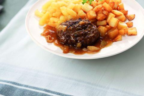 Hamburger in uiensaus met appelmoes en gebakken aardappelschijfjes